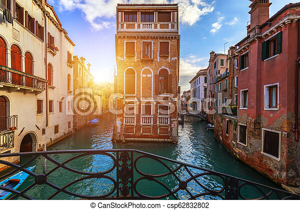 Street canal in Venice, Italy. Narrow canal among old colorful brick houses in Venice, Italy. Venice postcard - csp62832802