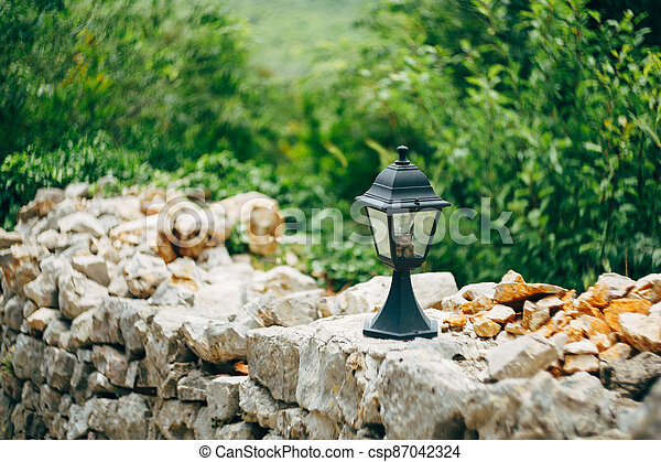 Street lamp on a stone fence against a background of green plants. - csp87042324