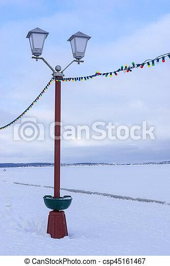 Street lamp on embankment of frozen lake - csp45161467