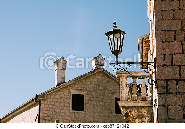 Street lamp on the wall of the building near the balcony against the blue sky. - csp87121042