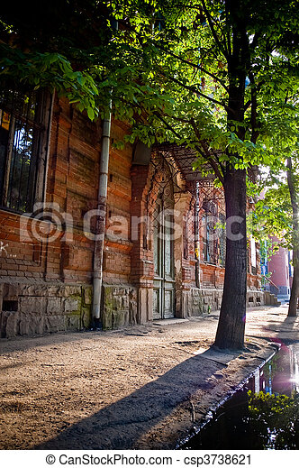 Street Of Krasnodar Russia Building Made Of Red Bricks Tree With Green Leaves Grows Next To Building Long Blue Shadow On