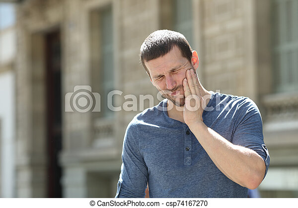 Stressed man suffering tooth ache in the street - csp74167270