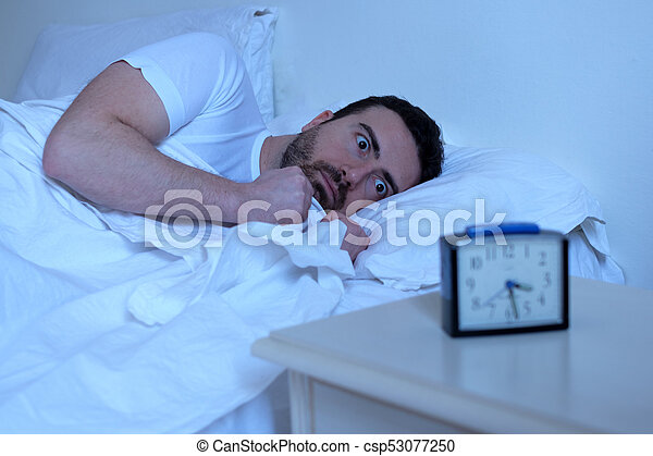 Stressed man trying to sleep in his bed - csp53077250