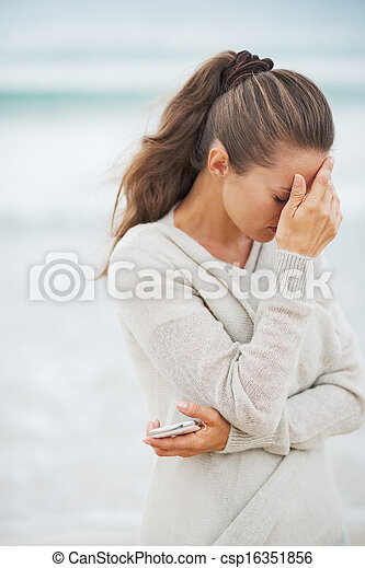 Stressed young woman in sweater on beach with mobile phone - csp16351856