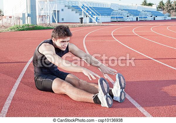 Un joven hace estirar a un atleta. Contra el fondo del estadio. - csp10136938