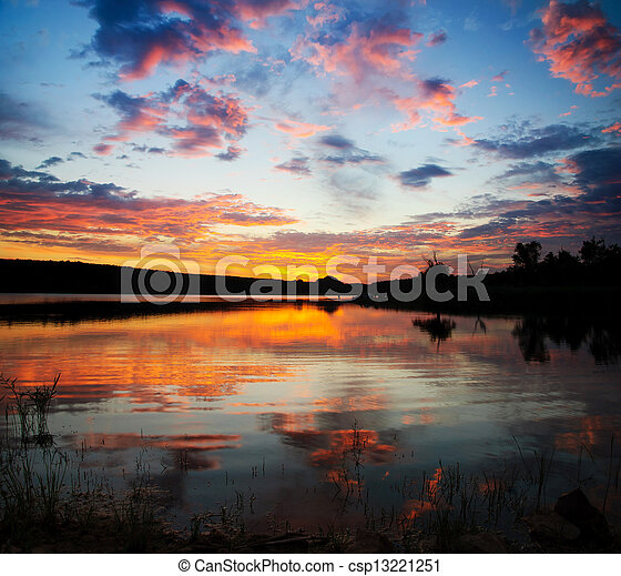Striking sunset above lake with bright clouds and sky - csp13221251