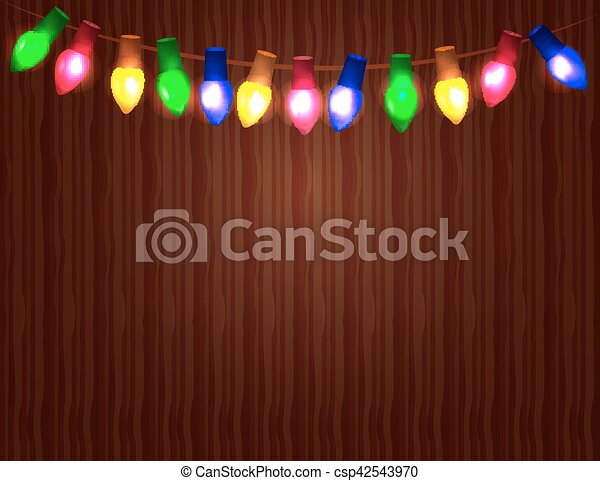 String of Color christmas light bulbs  on wooden background. - csp42543970