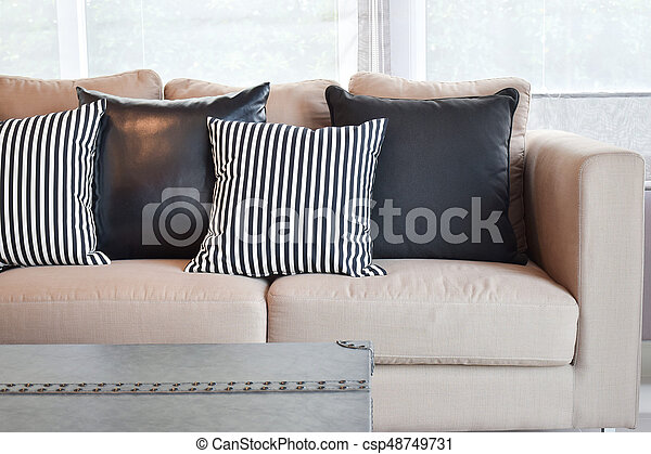 Striped and black leather pillows on velvet beige sofa in modern industrial  style living room