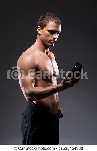 Strong, fit and sporty bodybuilder man with a bottle of sport supplements - csp35454388