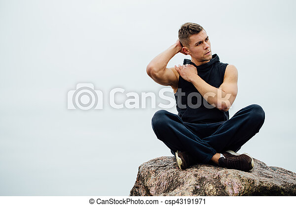 strong fitness yoga man in lotus pose on the rock beach