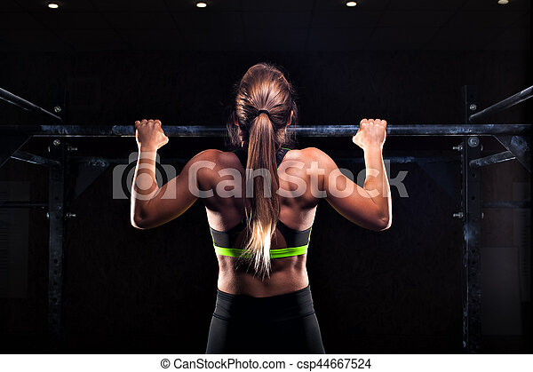 Strong girl in sportswear doing pull up exercise - csp44667524