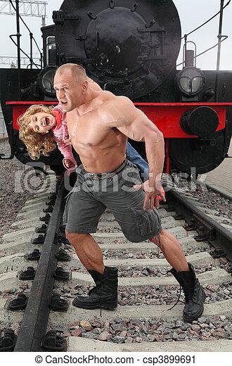 strong shirtless man saving little girl  on railroad - csp3899691