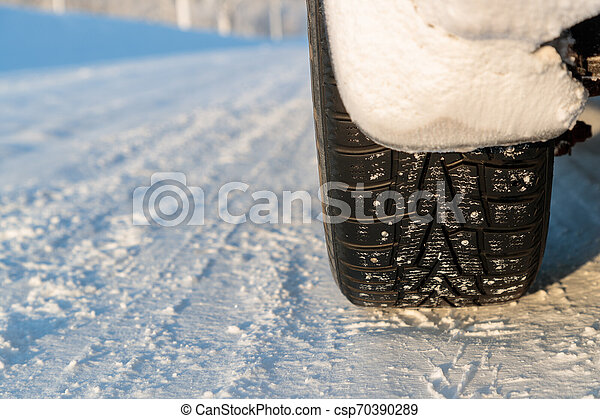 studded car wheel in winter on the road - csp70390289