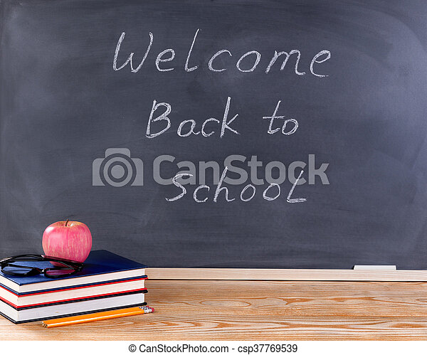 Student desktop and erased black chalkboard with welcome back to school  message