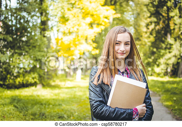 Student girl outdoors going back to school and smiling - csp58780217