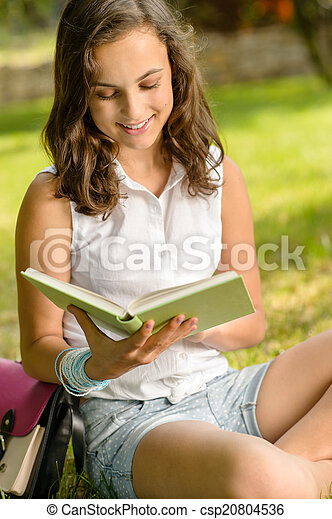 Student girl reading book in park summer - csp20804536