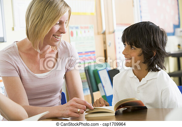 Student in class reading book with teacher - csp1709964
