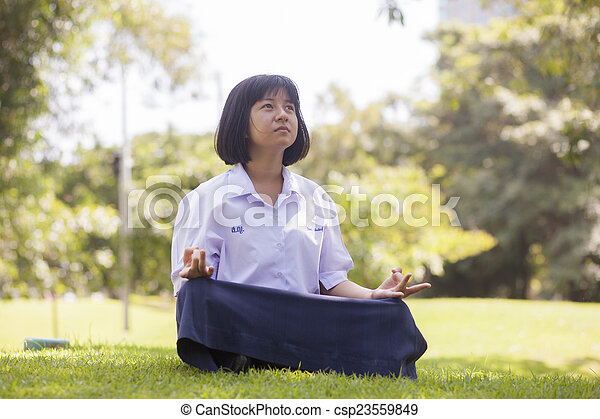 Student is sitting on the lawn. - csp23559849