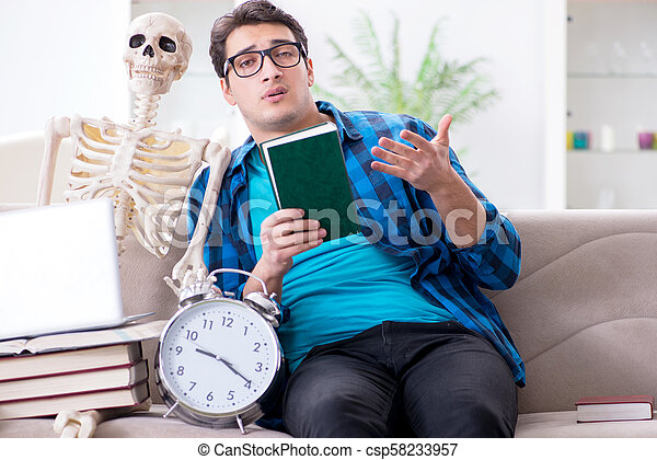 Student studying with skeleton preparing for exams - csp58233957