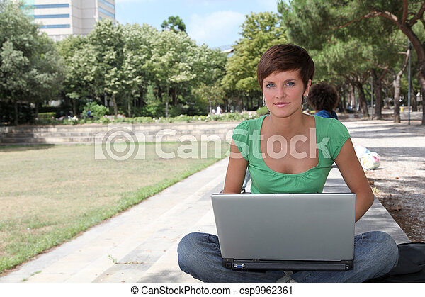 Student with laptop computer in college park - csp9962361