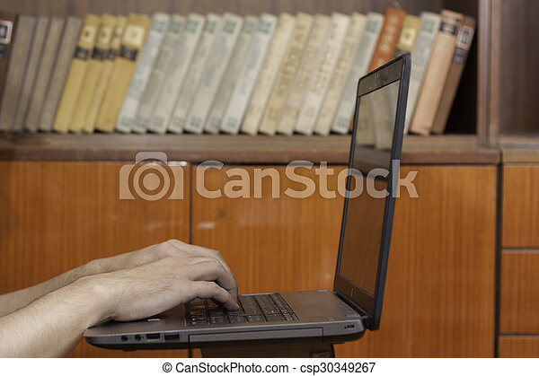 Student working on laptop in library - csp30349267