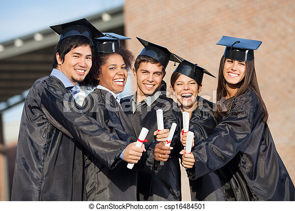 Students In Graduation Gowns Showing Diplomas On Campus - csp16484501