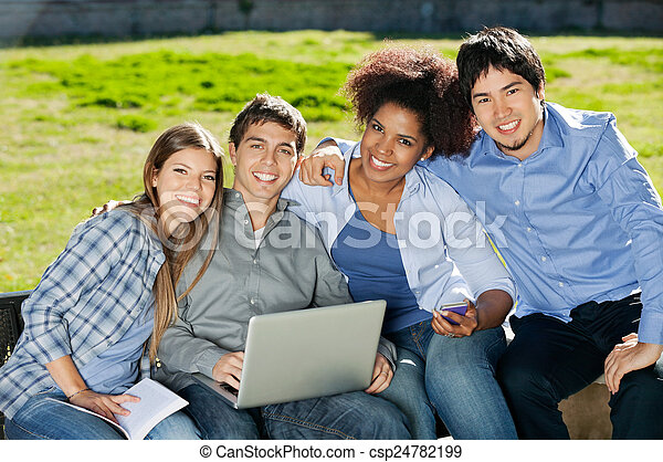 Students With Laptop And Book Sitting In College Campus - csp24782199