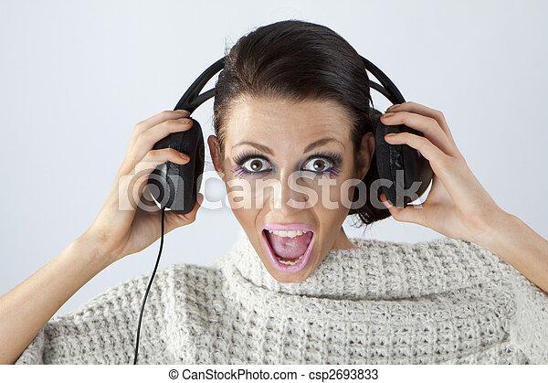 Studio portrait of a girl in headphones listening music - csp2693833