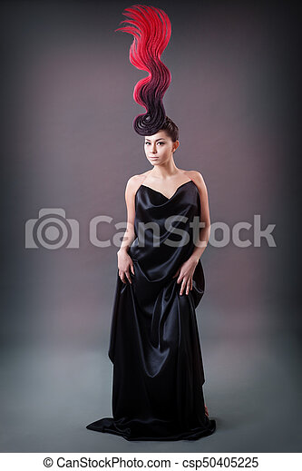 studio portrait of a girl with a fiery hairdo - csp50405225