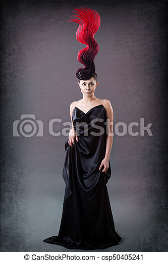 studio portrait of a girl with a fiery hairdo - csp50405241