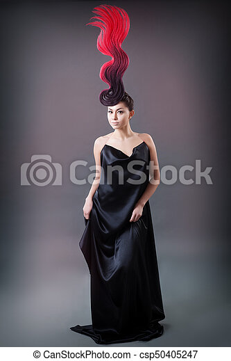 studio portrait of a girl with a fiery hairdo - csp50405247