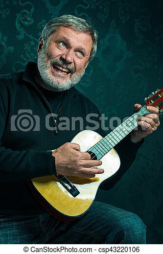 Studio portrait of senior man with guitar. - csp43220106