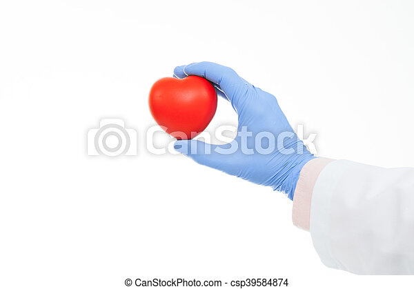 Studio shot of a doctor hand in a rubber glove holding heart shaped toy - csp39584874