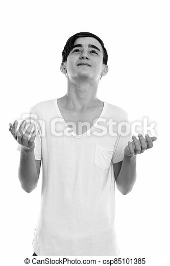 Studio shot of young handsome Persian teenage boy shrugging shoulders while looking up - csp85101385