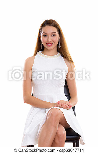 Studio shot of young happy beautiful Asian woman smiling while s - csp63047714