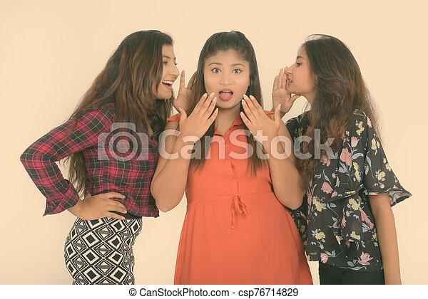 Studio Shot Of Young Happy Persian Woman Smiling While Looking Shocked With Both Friends Whispering On Each Side Studio Shot