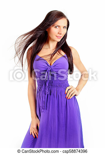 Studio shot of young woman in purple dress with wind in her hair isolated on white background. - csp58874396