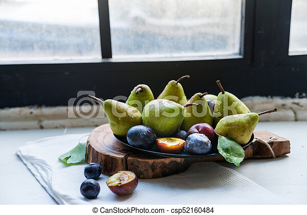 Studio shot plums and pears on plate heathy diet - csp52160484