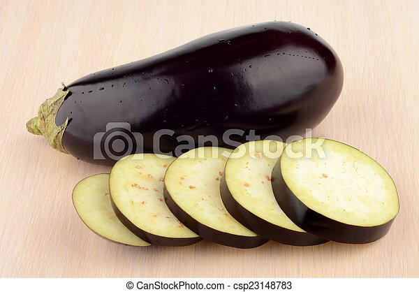Studio shot single wet aubergine eggplant on wooden table - csp23148783
