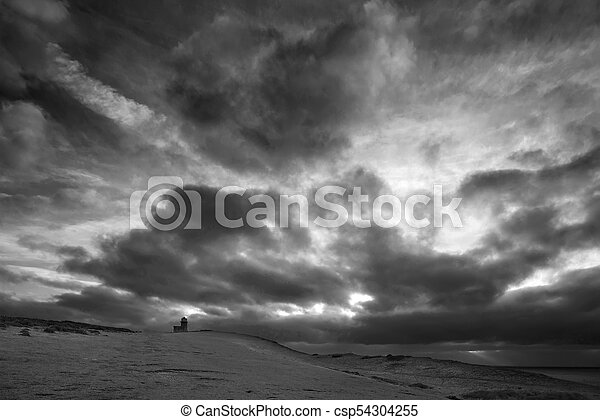 Stunning black and white landscape image of Belle Tout lighthouse on South Downs National Park during stormy sky - csp54304255