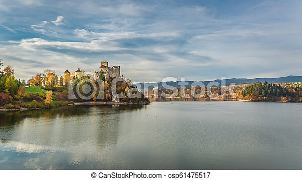 Stunning castle by the lake at dusk in autumn - csp61475517