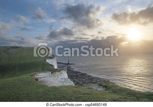 Stunning landscape image of Beachy Headt lighthouse on South Downs National Park during stormy sky - csp54693149