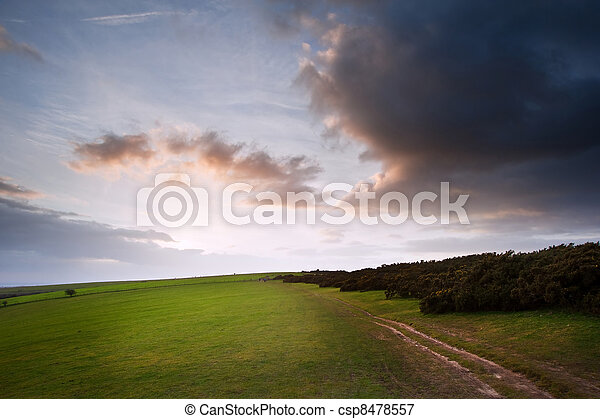 Stunning moody sky with beautiful cloud formations and colors over countryside landscape of path leading into distance - csp8478557