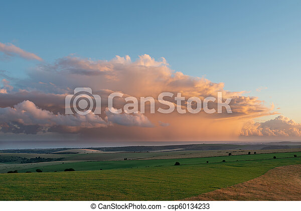 Stunning Summer sunset landscape image of South Downs National Park in English countryisde with orange rain clouds out to sea - csp60134233