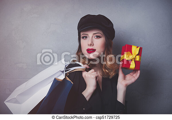 Style redhead girl in hat with shopping bags and gift box on grey background