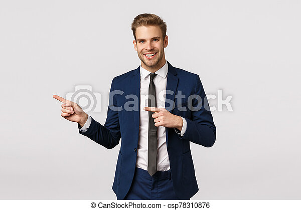 Stylish and confident, handsome blond bearded man in classic blue suit, pointing left, showing business partner place where discuss meeting, invite come inside office, standing white background - csp78310876