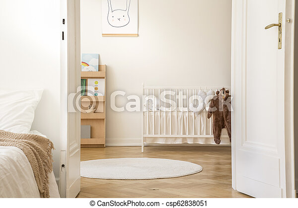 Stylish Bedroom Interior With Open Door To Scandinavian Nursery With White Crib Poster On The Wall And Carpet On The Floor Canstock