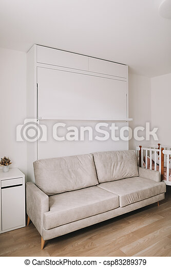 Stylish beige cozy room with sofa, table, baby crib, furniture. Modern interior design. Comfortable living room. Real photo - csp83289379