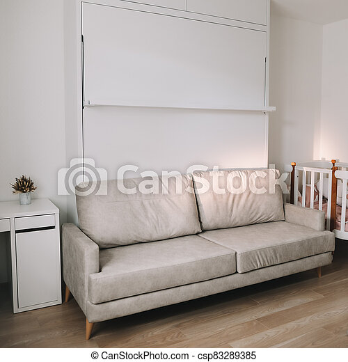 Stylish beige cozy room with sofa, table, baby crib, furniture. Modern interior design. Comfortable living room. Real photo - csp83289385