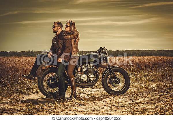 Stylish cafe racer couple on the vintage custom motorcycles in a field. - csp40204222